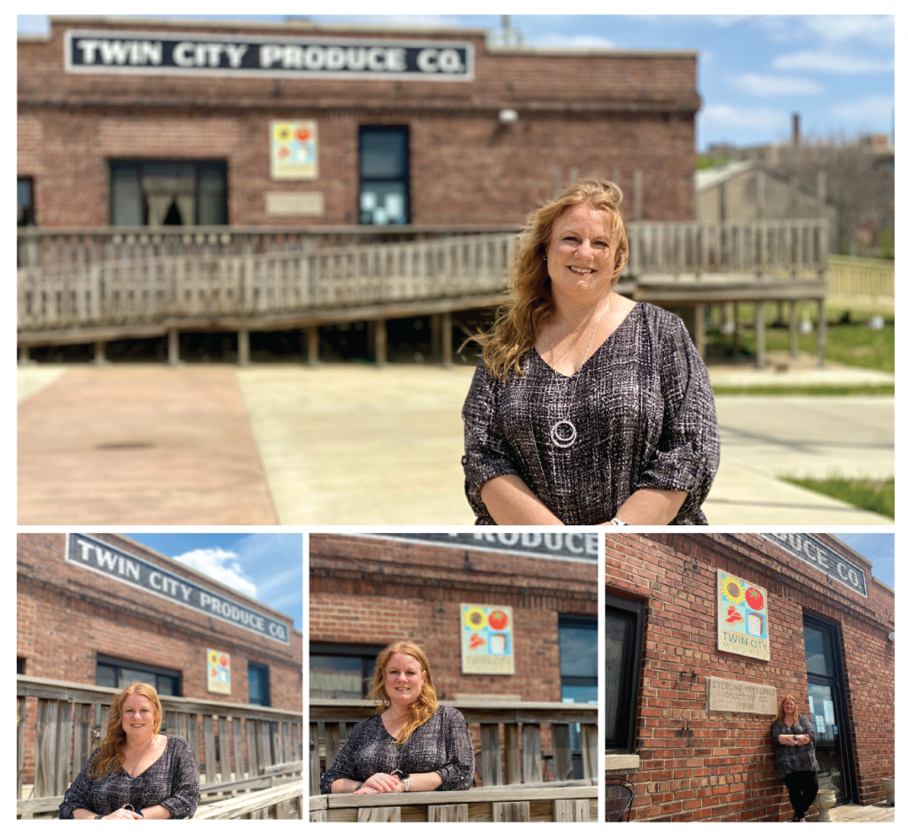 Female small business owner stands next to her store's large brick building  exterior on a sunny day as part of the dream big small business campaign.