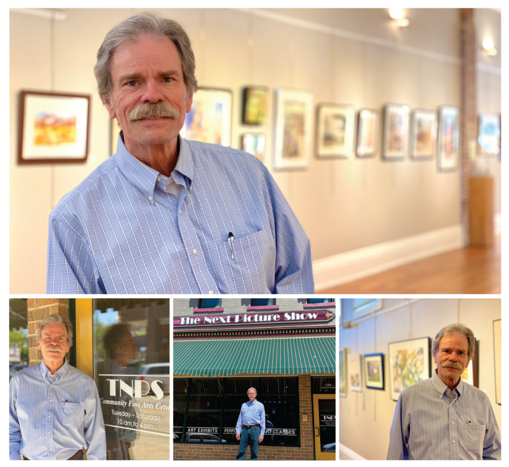 Older male business owner stands in an art gallery with several paintings on the wall in the background.