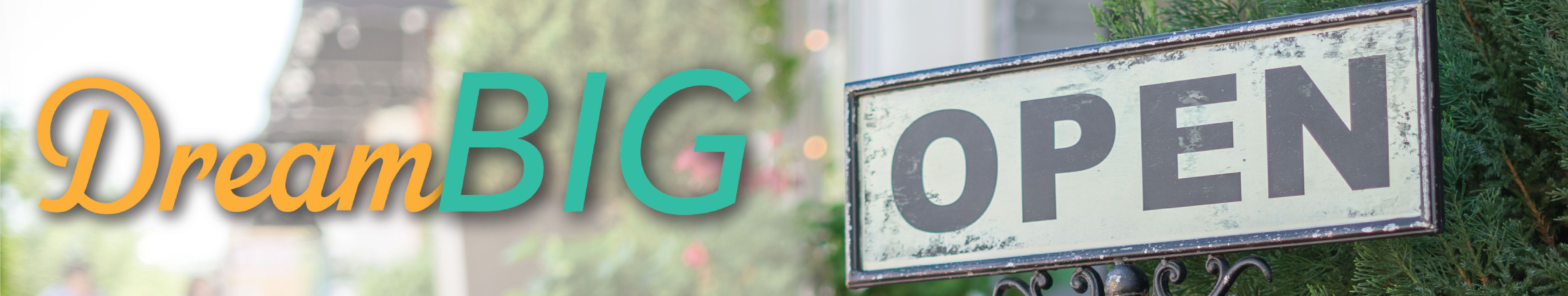 Grey sign with the word Open used outside a business surrounded by lush greenery and plants. The word dream in dark orange script font and the word Big all capital letters in mint green serif font.